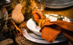 Place setting for Thanksgiving dinner with dishes, napkin, and centerpiece gourds