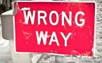 Red and white traffic sign says WRONG WAY.