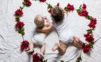 overhead shot of two babies laying in flowers strung into shape of a heart