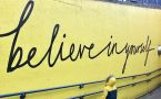 A child in yellow coat looks up at painted yellow wall that says BELIEVE IN YOURSELF