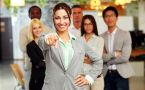 Business woman in front of team pointing at camera.