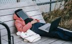 Woman asleep outdoors with book over face and computer on her lap.