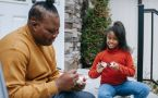 Father and daughter make Christmas crafts on porch.