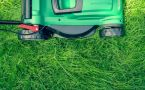 Overhead of lawn mower in green grass.