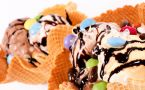 Two gooey waffle cone ice cream sundaes with colorful toppings.