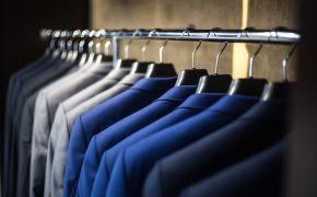 Row of blue and gray sport coats on clothes hangers