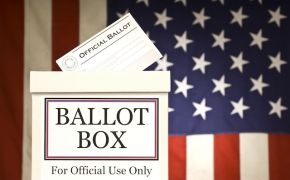 Ballot box with ballot going into slot, in front of American flag.