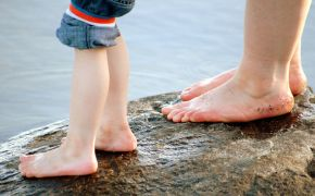 adult and child bare feet on wet rock