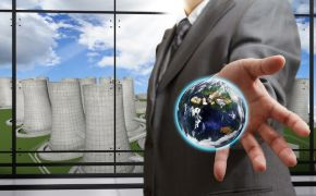 Torso of businessman holding earth in hand before window looking at nuclear reactors.