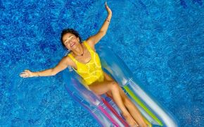 Happy woman reclining on floating lounger in pool