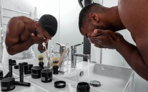 A man rinsing his face in the sink in front of mirror.