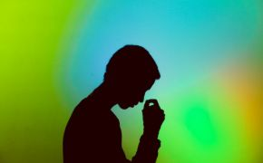 Silhouette of stressed man against colorful blue and green background