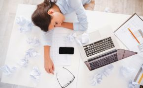 Woman asleep at desk with computer, papers, etc.