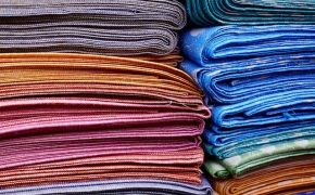 Stacks of multi-colored hand-woven fabrics.