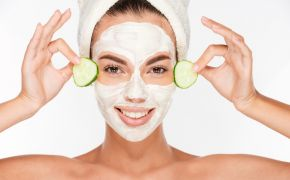 Woman with face mask and hair towel holding cucumber slices by her eyes.