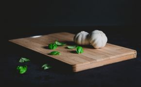 Garlic and basil on wooden cutting board.