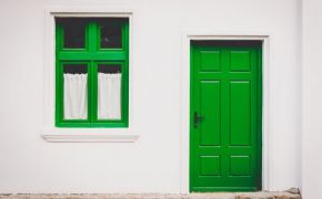 Bright green door and window in white home.