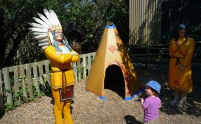 child looking at Native American statue with headdress
