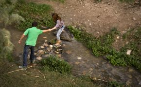 man and woman helping each other across stream