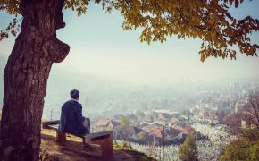 Lonely man sitting alone on bench overlooking village