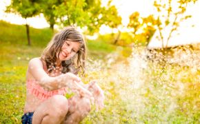 Girl playing in sprinklers on a sunny day