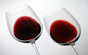two tilted wine glasses with red wine