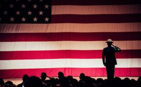 Silhouette of soldier saluting huge American flag.