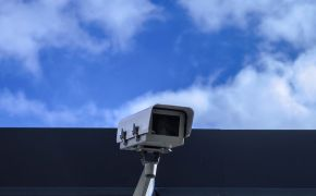 Security camera against blue clouded sky.
