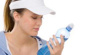 Woman in visor reading label of plastic water bottle.