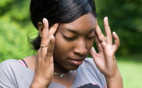 Anxious woman with fingers on her temples, stressed out.