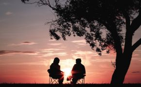 Silhouette of two retirees watching sunset from under a tree