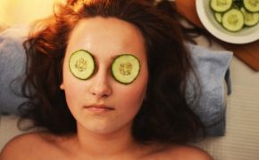 Woman in spa with cucumbers over eyes.