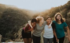 Women laughing arm in arm outdoors.