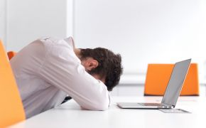 Overwhelmed man with head down on desk