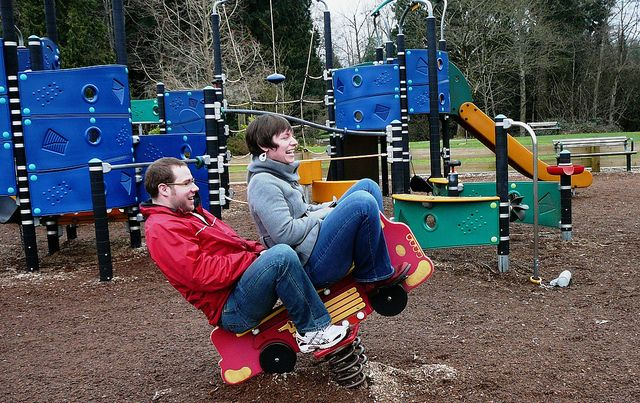 man and woman playing on playground equipment