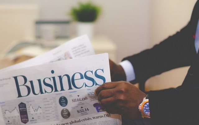 Man's hands holding BUSINESS section of newspaper.