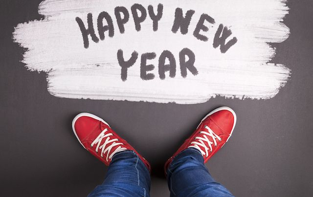 Red sneakers on black floor with chalk reading HAPPY NEW YEAR