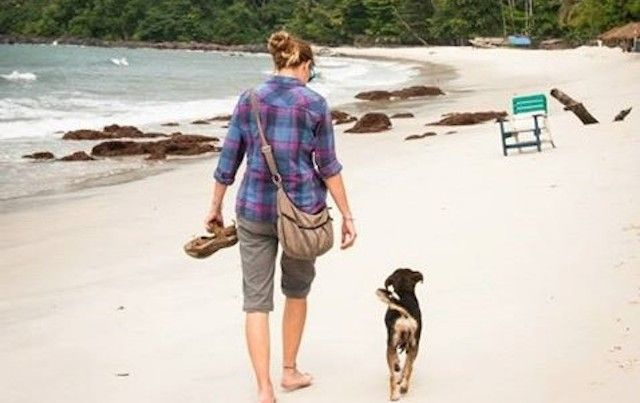 rear view of woman walking with dog on Sierra Leone beach
