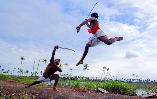 Two men in India do outdoor demonstration of sword skills.