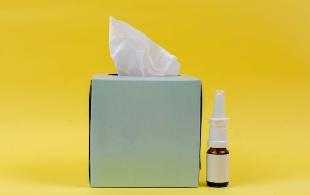 Box of tissues and allergy nasal spray against yellow background.
