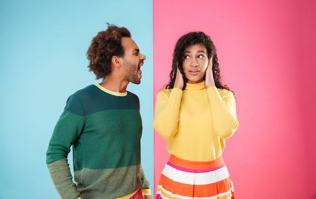Man and woman arguing in front of pink and blue wall.