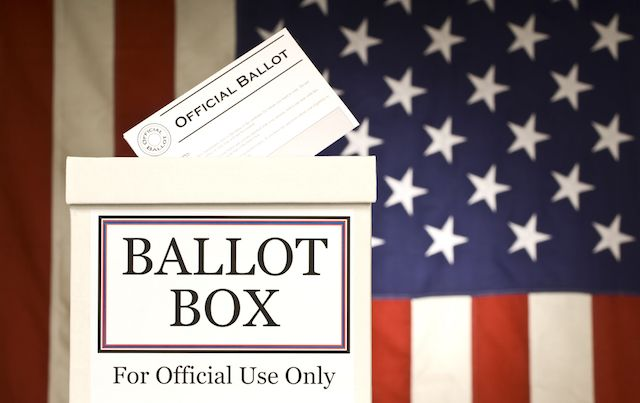 Ballot box in front of American flag.