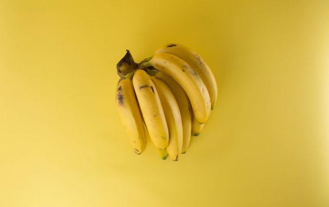 Yellow bunch of bananas on matching yellow backdrop