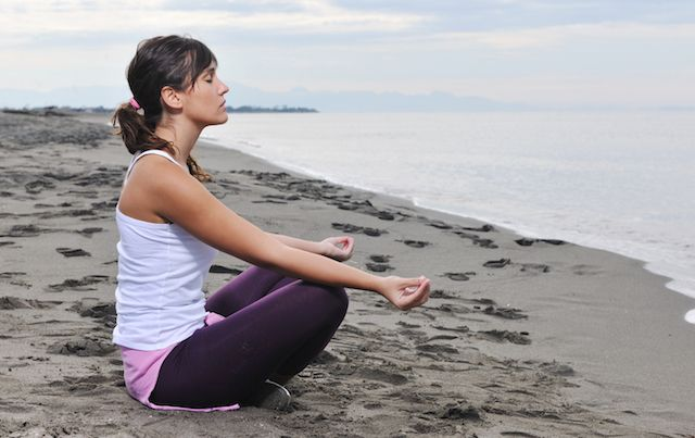 Woman meditating while sitting in the sand at the beach