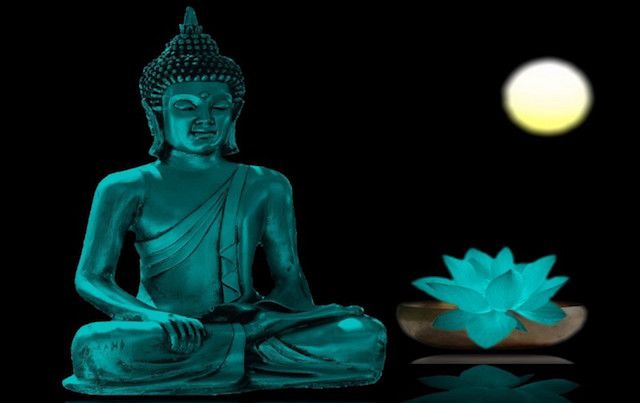 Buddha statue meditating in blue light with full moon and lotus.