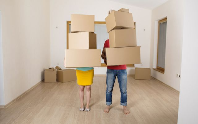 Man and woman holding huge stacks of cardboard boxes