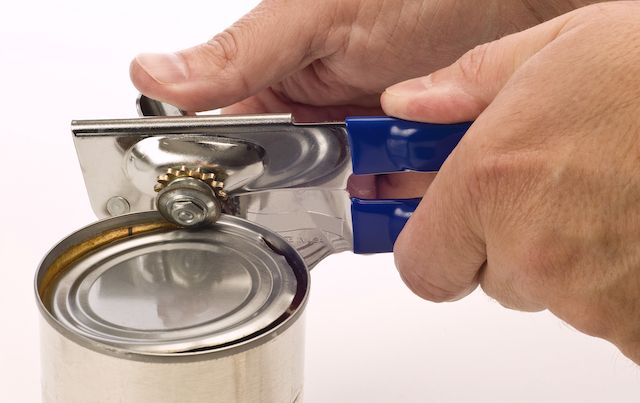 Close up of hands using can opener to open food can