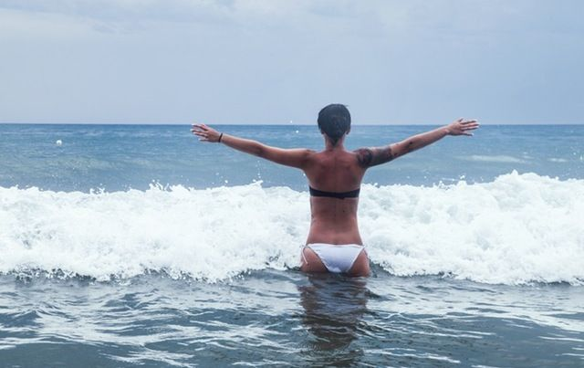 woman from back standing in surf, arms outstretched