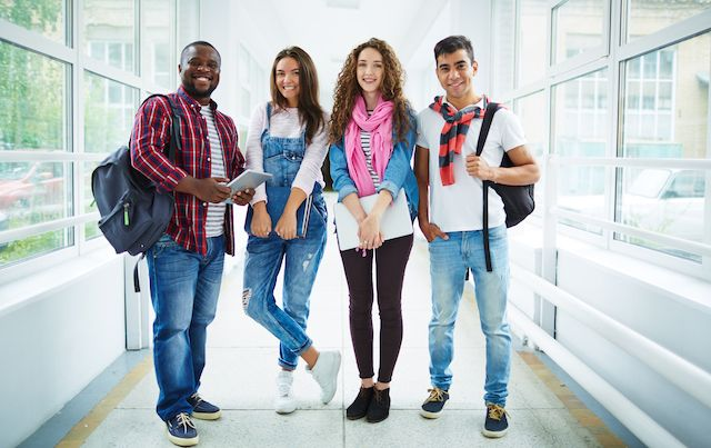 Group of four college students standing together in hallway.
