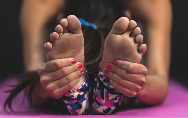 Close up of woman grabbing feet in yoga pose